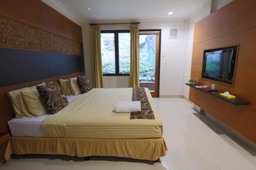 A bed or beds in a room at Taman Safari Lodge