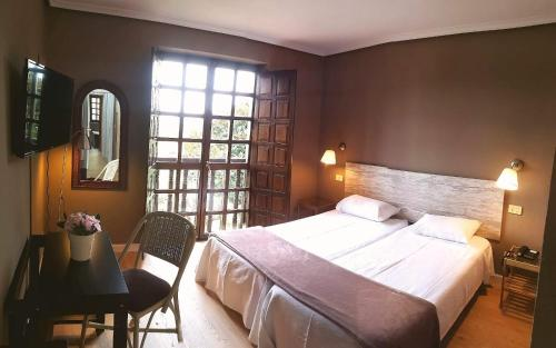 A bed or beds in a room at Hotel Colegiata