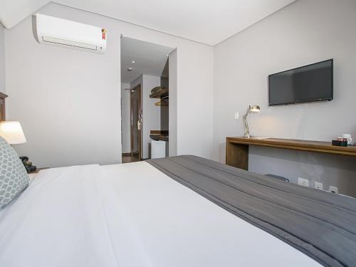 A bed or beds in a room at Flame Hotel Canela