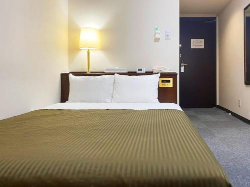 A bed or beds in a room at Hotel Trend Matsumoto