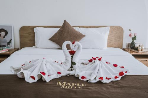 A bed or beds in a room at Maple Suite Hotel & Apartment