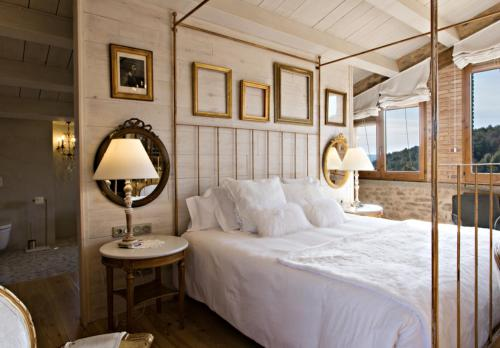 A bed or beds in a room at La Vella Farga Hotel