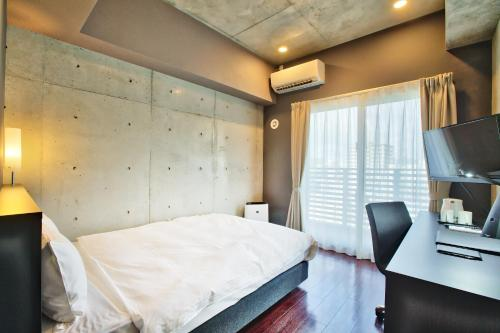 A bed or beds in a room at NAHA-WEST INN