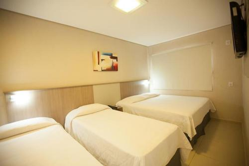 A bed or beds in a room at Iguassu Express Hotel