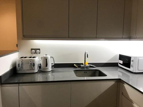 A kitchen or kitchenette at Maplewood luxurious one-bed flat with free parking