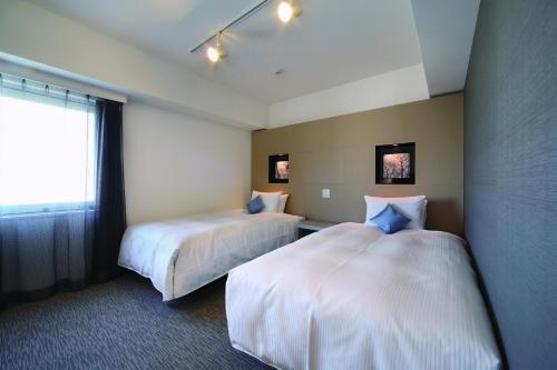 A bed or beds in a room at Hotel Vista Sapporo Odori