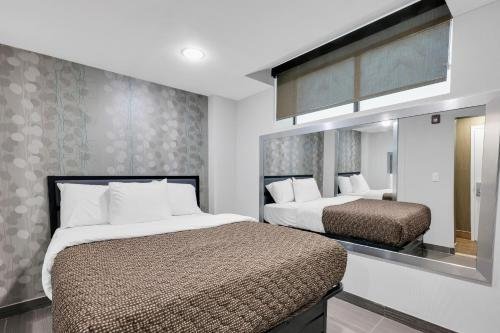 A bed or beds in a room at Hotel Mint JFK Airport