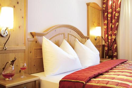 A bed or beds in a room at Hotel Wittelsbach Oberammergau