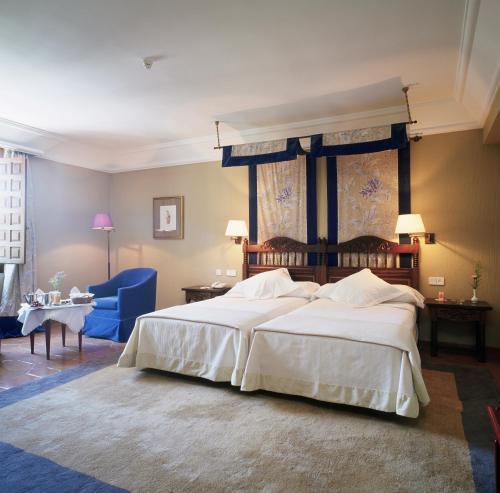 A bed or beds in a room at Parador de Cuenca