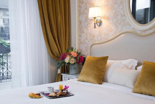 Een bed of bedden in een kamer bij Hôtel Saint-Pétersbourg Opéra & Spa