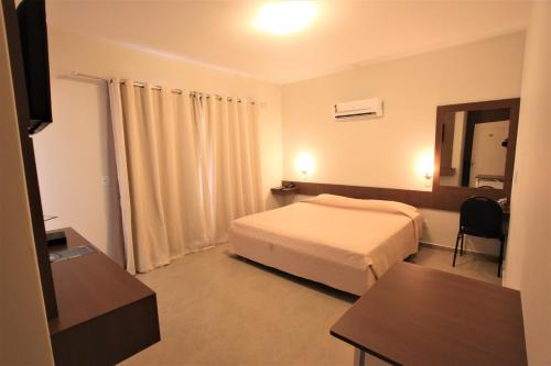 A bed or beds in a room at Hotel Fernandão