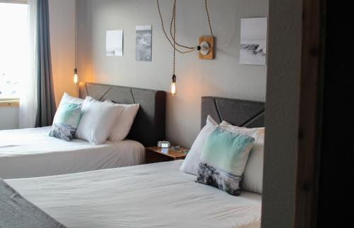 A bed or beds in a room at Adrift Hotel