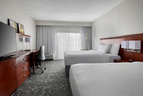 A bed or beds in a room at Courtyard by Marriott Lincroft Red Bank