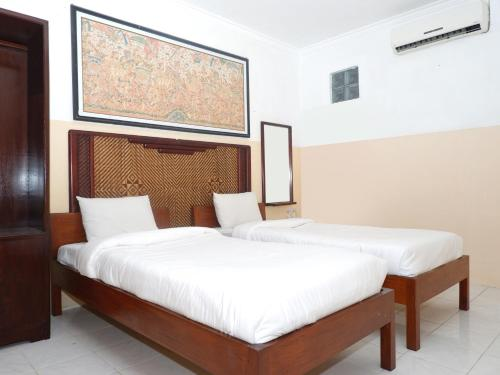 A bed or beds in a room at Rajasa Hotel