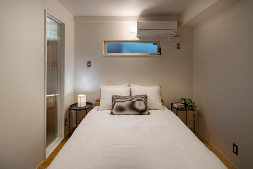 A bed or beds in a room at Japan Sessions KANZAKI 02
