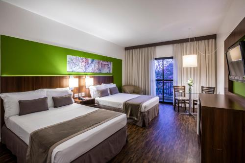 A bed or beds in a room at Hotel Panamby Guarulhos