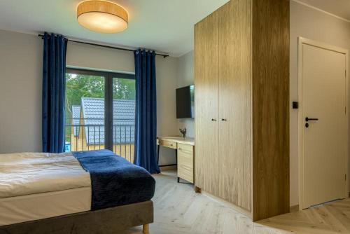 Łóżko lub łóżka w pokoju w obiekcie Zapach Drewna Domy na Mazurach
