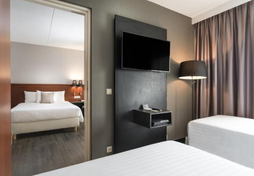 A bed or beds in a room at Courtyard by Marriott Amsterdam Airport