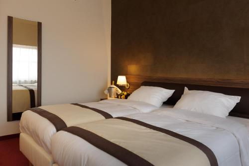 A bed or beds in a room at Golden Tulip Hotel de' Medici