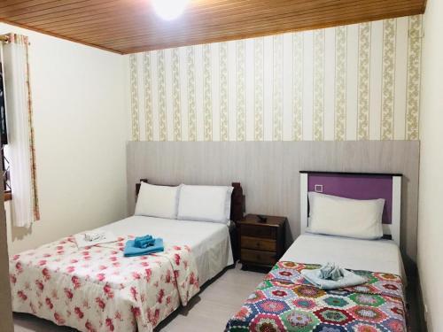 A bed or beds in a room at Pousada Recanto da Giovana