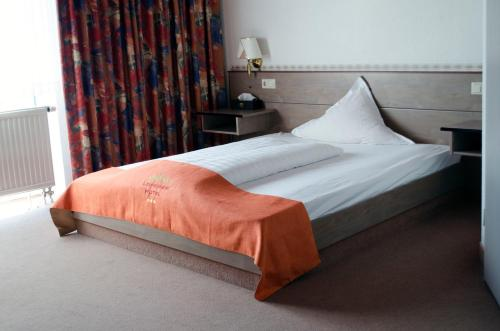 A bed or beds in a room at Leipziger Hotel