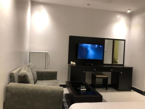 Uma TV ou centro de entretenimento em اجنحة المسكن المثالي الفندقية