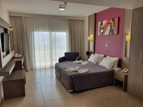 A bed or beds in a room at New Famagusta Hotel & Suites