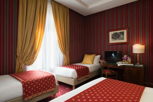 A bed or beds in a room at Atlante Garden Hotel