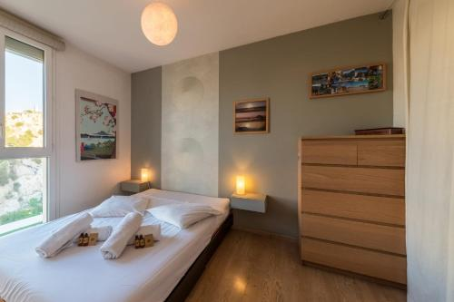 A bed or beds in a room at Superb flat with a magnificent view from the terrace in Marseille - Welkeys