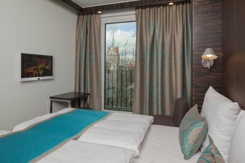 A bed or beds in a room at Motel One Rostock