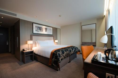 A bed or beds in a room at Clayton Hotel Chiswick