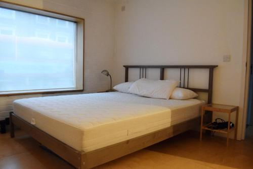 A bed or beds in a room at Modern Cosy 2 Bedroom House with Roof Terrace
