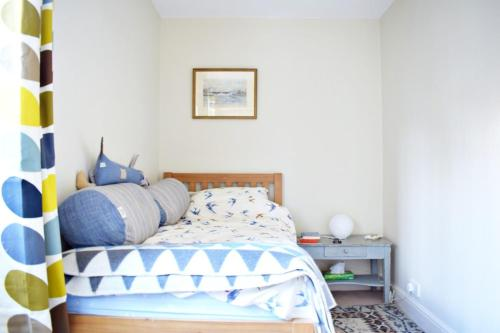 A bed or beds in a room at Charming 2 Bedroom Home 3 mins from Arsenal Station