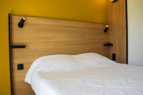 A bed or beds in a room at Premiere Classe Rodez