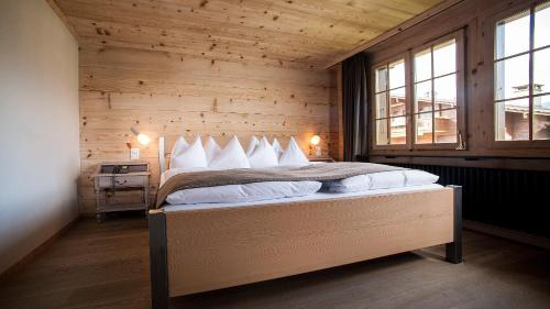 A bed or beds in a room at Hotel Arc-en-ciel Gstaad