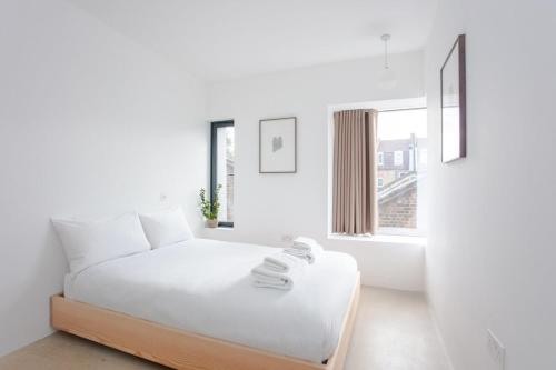 A bed or beds in a room at Chic Modern 2 Bedroom Flat in Stoke Newington