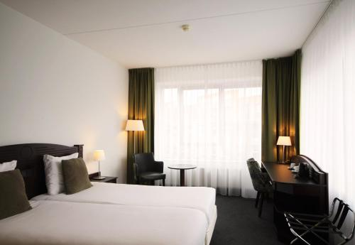 A bed or beds in a room at Amrâth Hotel Alkmaar