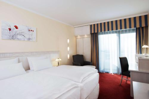 A bed or beds in a room at NH Wiesbaden