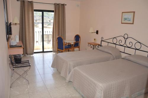 A bed or beds in a room at Porto Azzurro Aparthotel