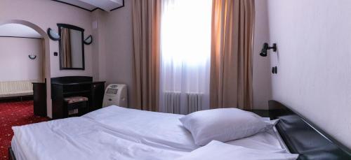 Un pat sau paturi într-o cameră la Hotel Aurora