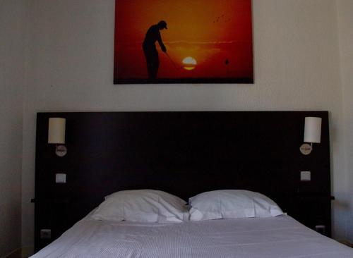A bed or beds in a room at Hôtel Les Tennis Men La Baule Les Pins centre
