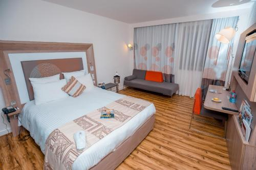 A bed or beds in a room at Accra City Hotel