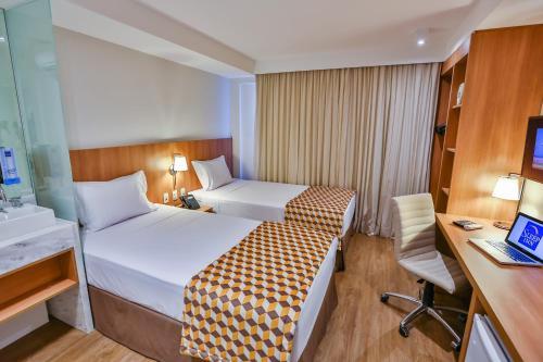 A bed or beds in a room at Sleep Inn Aeroporto de Guarulhos - São Paulo