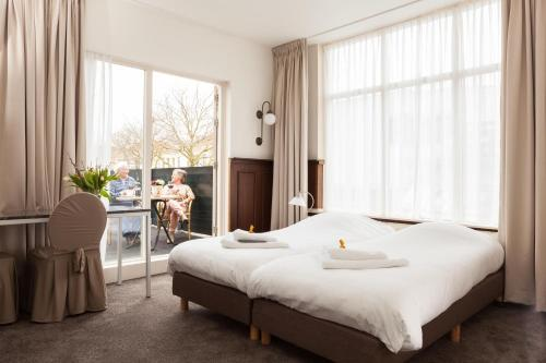 A bed or beds in a room at Hotel Stad en Land