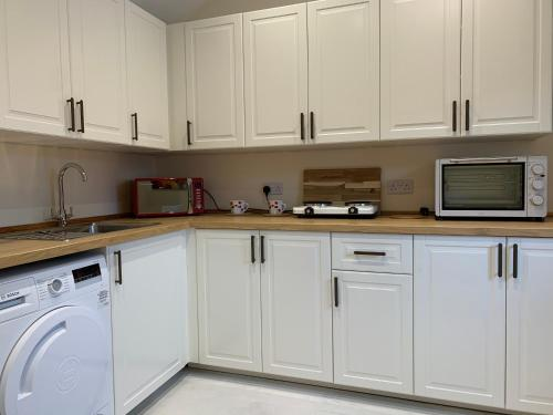 A kitchen or kitchenette at Handywater Cottages