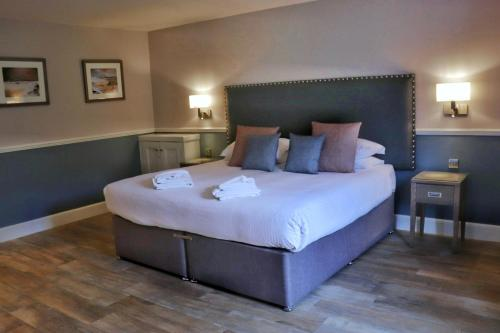 A bed or beds in a room at Balmacara Hotel
