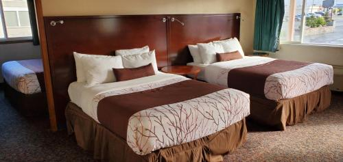 A bed or beds in a room at Olympic Inn & Suites