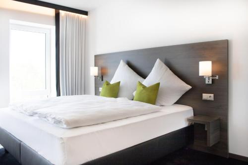 A bed or beds in a room at KU Hotel