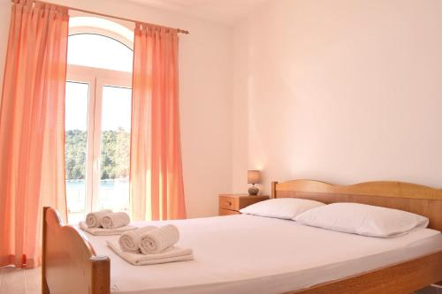A bed or beds in a room at Mljet Sunset Apartments