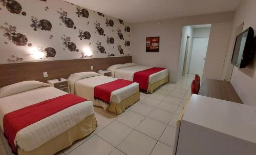 A bed or beds in a room at Foz Plaza Hotel